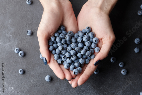 Close up of woman hands holding fresh blueberries. Healthy eating, dieting and vegetarian food concept.