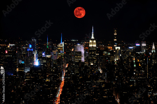 Dramatic picture of lunar eclipse over the skyline of Midtown Manhattan, New York City at night as can be seen from Downtown