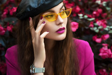 Outdoor Close Up Fashion Portrait Of Young Beautiful Woman Wearing Trendy Yellow Sunglasses, Leather Beret, Wrist Watch, Fuchsia Color Blazer, Posing Near Blooming Pink Flowers