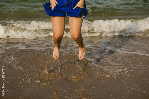 Fotografie, Obraz  Legs of woman in blue dress jumping on the shore of the beach