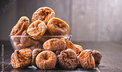 Composition with bowl of dried figs on wooden table