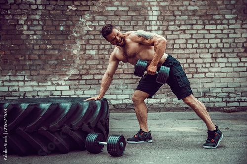 Athletic man working out with a dumbbell in front of brick wall Tapéta, Fotótapéta