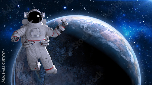 Fotografie, Obraz  Astronaut in space giving thumbs up, cosmonaut floating above planet Earth, 3D r