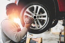 Asian Young Mechanic Working Holding The Device Changing Tyre Of Car. Repair Service..