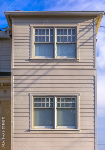 Two upper stories of white buildings with panels