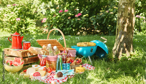 Fotografia Small grill and tree trunk next to picnic blanket