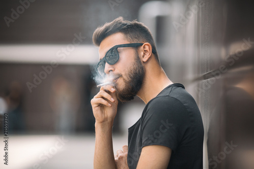 Fotomural A young handsome white bearded man in black t-shirt smokes a cigarette in the street in the spring