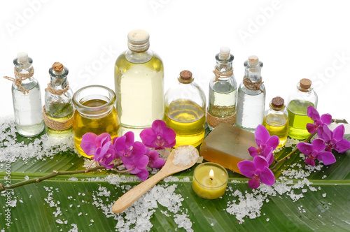 Spa setting on banana leaf with pink orchid ,candle, salt in spoon ,bottle oil