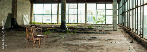Foto op Canvas Oude verlaten gebouwen Industrial interior at the old electronic devices factory with big windows and empty floor. Interior inside an abandoned factory, overgrown with green moss and plants.