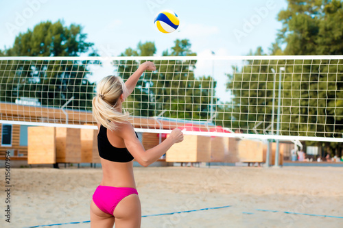Athletic blonde woman playing volleyball near the net on the beach. Empty space