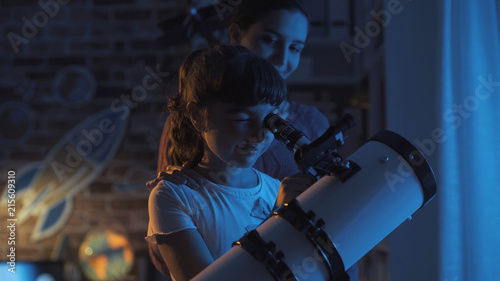 Cute sisters watching the stars with a telescope - 215609310