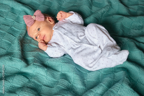 Fotografía Newborn baby girl with bow in white footed pajamas
