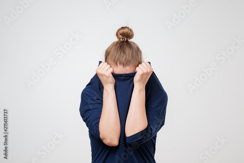 Fotomural European woman hiding face under the clothes
