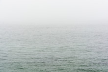 Flat Grey Sea With Wavelets Disappearing In The Fog.