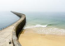 The Mole Des Noires, The Long Breakwater Of The Walled City Of Saint-Malo In Brittany, France, And The Mole Beach By A Sunny And Misty Weather.