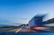 Leinwandbild Motiv Background photograph of a highway. Truck on a motorway, motion blur, light trails. Evening or night shot of trucks doing logistics and transportation on a highway.