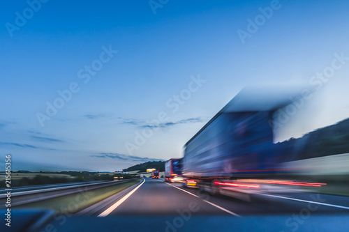 Fototapeta Background photograph of a highway. Truck on a motorway, motion blur, light trails. Evening or night shot of trucks doing logistics and transportation on a highway. obraz