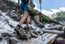 Woman Hiking In The Alps, Wearing Outdoor Boots And Shorts Walking Across A Wooden Bench And Rocks Crossing A Wild Alpine Creek Using Hiking Poles. Trekking Shoes On Rocks And In Running Water.