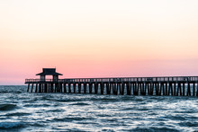 Naples, Florida Pink And Yellow Pastel Sunset In Gulf Of Mexico With Pier, Wooden Jetty, With Many Pillars Over Horizon And Dark Blue Ocean Waves