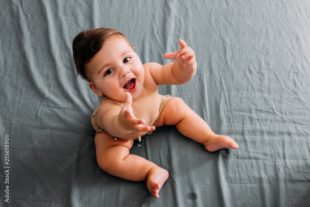 Fototapety, obrazy: Top view of smiling baby sitting on the bed in the room wearing shorts