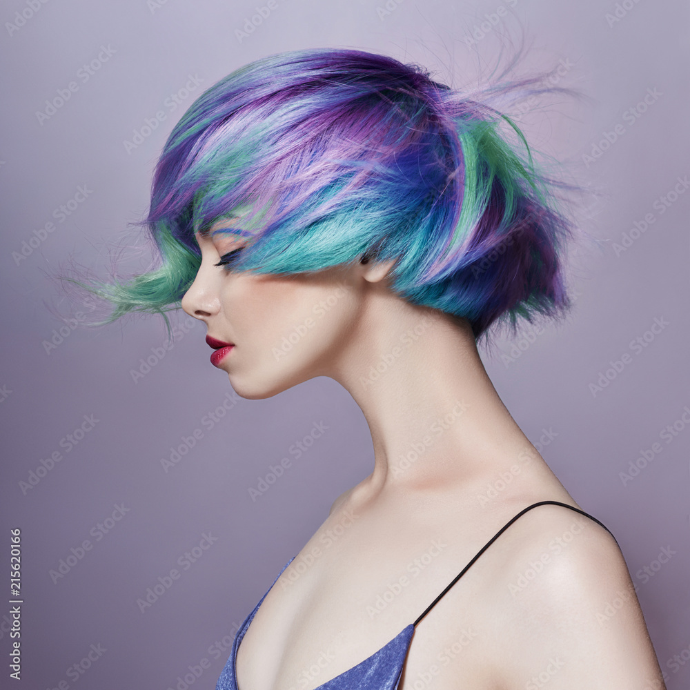 Fototapeta Portrait of a woman with bright colored flying hair, all shades of purple. Hair coloring, beautiful lips and makeup. Hair fluttering in the wind. Sexy girl with short hair