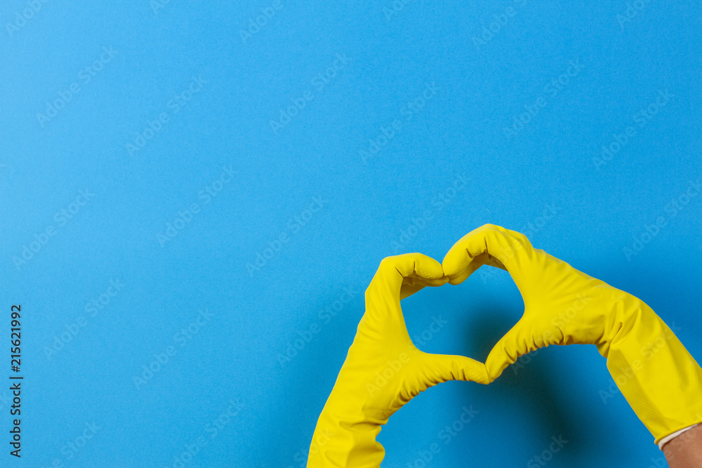 Fototapety, obrazy: Hands in yellow rubber gloves making heart shape with fingers, on blue background
