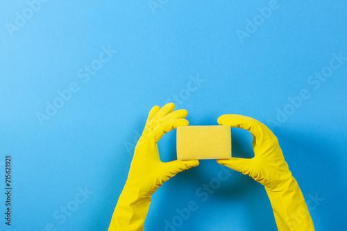 Vászonkép Hands in yellow gloves holding sponge on blue background