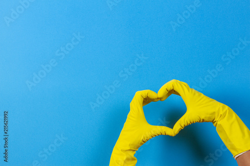 Fototapeta Hands in yellow rubber gloves making heart shape with fingers, on blue backgroun