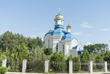 Orthodox Temple With Blue Roof And Golden Domes In A Picturesque Place Against The Blue Sky