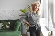 Leinwanddruck Bild - People, age, beauty, style and fashion concept. Indoor shot of fashionable gorgeous middle aged female model wearing stylish elegant striped blouse and black trousers posing at home by the window