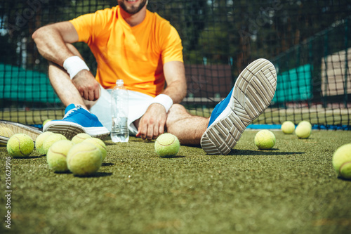 Fotobehang Voetbal Happy man tasting appetizing beverage while relaxing after tennis. Sport equipment situating near him