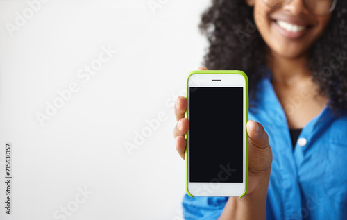 Modern lifestyle and technology concept. Cropped shot of dark skinned young female with wavy hair holding cell phone with black copyspace screen, posing at white blank studio wall. Film effect