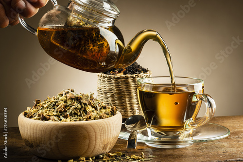 glass teapot pouring tea into glass cup on wooden table