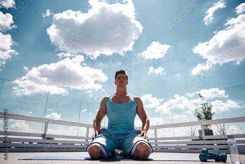 Foto op Canvas Ontspanning Low angle of strong athlete is kneeling on sunny terrace and putting hands on legs. He is closing eyes for relaxing after exercising with dumbbells. Refreshing mind and body after work out concept