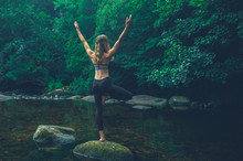 Yoga Woman In Tree Pose On Rock In River