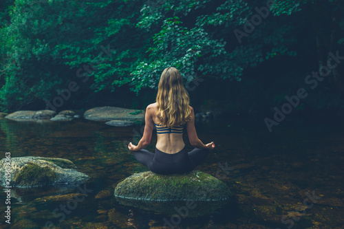 Fotografia  Woman meditating on rock in river