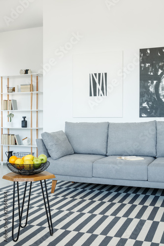 Staande foto Hoogte schaal Grey sofa and table on patterned carpet in bright living room interior with posters. Real photo