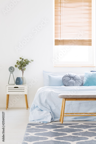 Window With Wooden Blinds In White Bedroom Interior With Bed With Light  Blue Bedclothes, Carpet