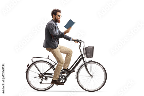 Young man riding a bicycle and reading a book