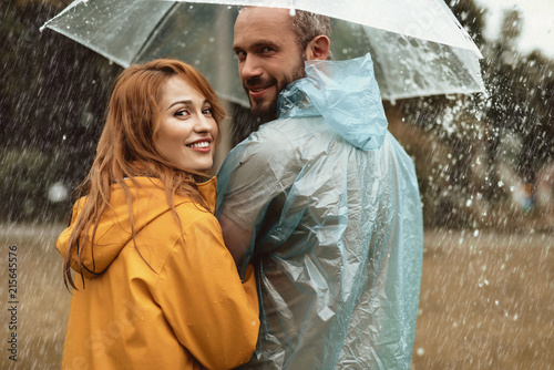 Fotografia Happy couple walking under umbrella hiding from rain