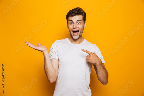 Fotografía  Portrait of a cheerful young man pointing fingers away