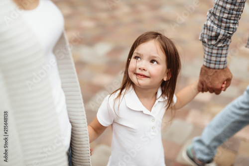 Waist up portrait of little kid looking at mom with joy. She is walking with mother and father holding hands and feeling delighted