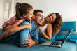 Leinwandbild Motiv Happy family lies on bed and watching something on laptop.Laughing and fun.