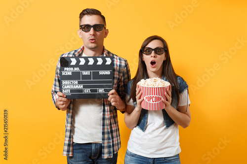 Young shocked couple woman man in 3d glasses watching movie film on date holding classic black film making clapperboard bucket of popcorn isolated on yellow background Wallpaper Mural