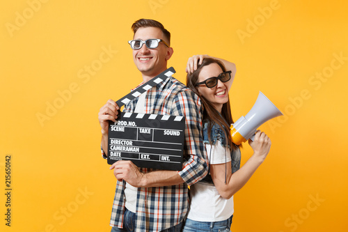 Photo  Young joyful smiling couple woman man in 3d glasses watching movie film on date holding classic black film making clapperboard and megaphone isolated on yellow background