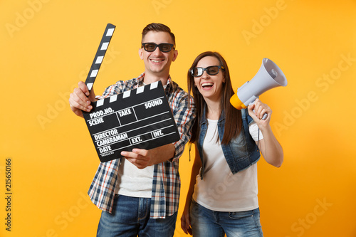Young happy smiling couple woman man in 3d glasses watching movie film on date holding classic black film making clapperboard and megaphone isolated on yellow background фототапет