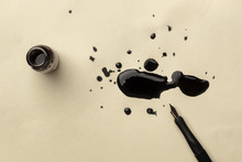 An Overhead Photo Of An Ink Well With Drops Of Ink And A Nib Pen, With Copy Space