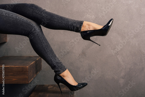 Carta da parati women's legs in jeans and high-heeled shoes on a wooden cantilever ladder
