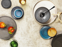Overhead View Of Plates, Bowls, Glasses And Spoon On Plaster Surface With Blood Oranges And Antler