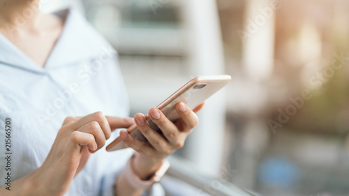 Fotomural  woman using smartphone on staircase in public areas, During leisure time
